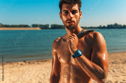 Plexiglas Fitness Portrait of young man resting after fitness workout at a beach on a sunny day.