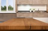 Kitchen, background. Empty textured wooden table and kitchen window shelves blurred background - 217291092