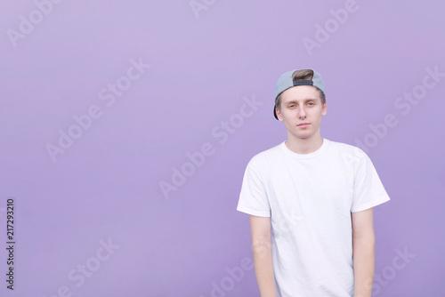 Hndome młody człowiek w białej koszulce i czapce stoi na tle pastelowej fioletowej ściany. Portret uczeń na purpurowym tle i patrzeć w kamerę.