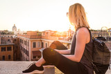 Fashinable female tourist with vintage hipster backpack admiring the beautiful view of at Piazza di Spagna, landmark square with Spanish steps in Rome, Italy at sunset.