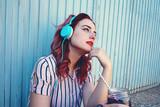 Mujer joven y pelirroja escuchando música con sus auriculares
