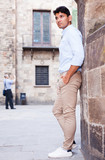 young European guy in blue shirt walking around city - 217307688