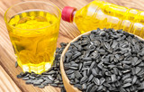 Glass and bottle of cooking oil with bowl of sunflower seeds on wooden table.