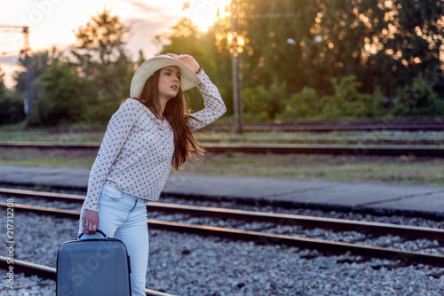 Fototapeta Young woman with luggage on train station waiting