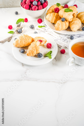 Foto Murales Sweet summer dessert, homemade baked mini croissants with berry jam, served with tea, fresh raspberries, blueberries and mint. On a white marble table, copy space
