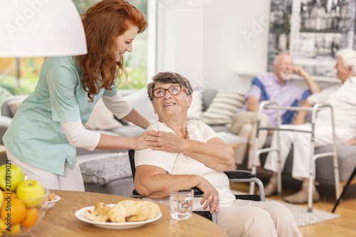 Friendly nurse supporting smiling senior woman in nursing house