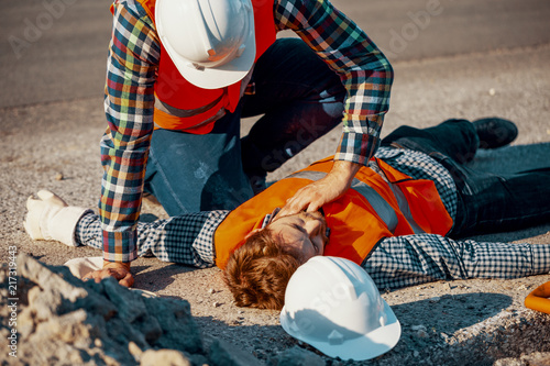Worker in white helmet checking life functions of the injured during roadworks