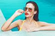 Leinwanddruck Bild - Sexy brunette retro woman licking lollipop in swimming pool