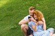 happy redhead couple with smartphones sitting on grassy meadow