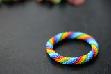 Kid's bracelet from beads of rainbow colors on a dark background close up - 217329477