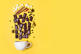 Hot chocolate cup, chocolate pieces, spices and marshmallows on yellow background - 217330034
