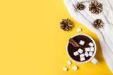 Hot chocolate cup with cinnamon and marshmallow on yellow background. Warming Christmas winter drink - 217330654