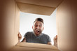 Leinwanddruck Bild - The surprised man unpacking, opening carton box and looking inside. The package, delivery, surprise, gift lifestyle concept. Human emotions and facial expressions concepts
