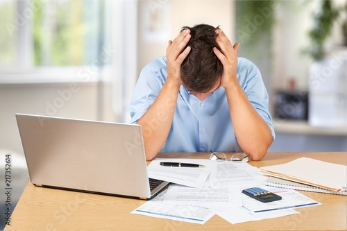 Leinwanddruck Bild Tired young businessman with stack of papers