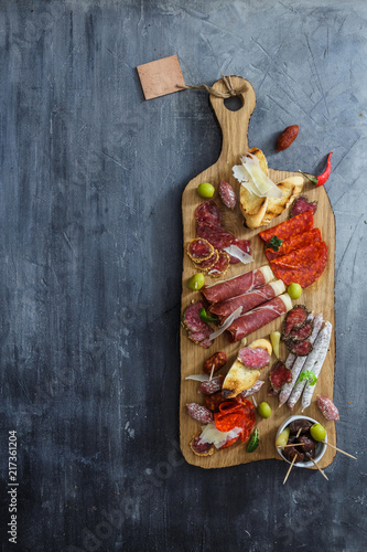 Typical spanish tapas concept. include variety slices jamon, chorizo, salami, bowls with olives, peppers. Copyspace. - 217361204