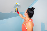 Woman at painting a room with paint roller - 217364881