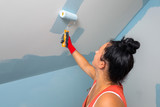 Woman at painting a room with paint roller - 217364891