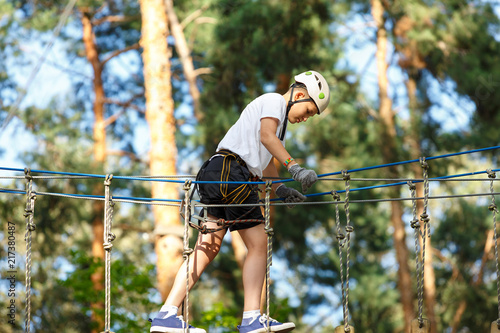 Foto Murales cute boy  in white t shirt in the adventure activity park with helmet and safety equipment. Young boy playing and having fun doing activities outdoors. Hobby, active lifestyle concept