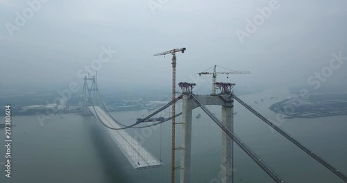 Fototapeta Mega bridge construction over the river in China Asia, with stationary boats anchored on the river.