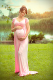 Pregnant happy woman caressing her belly in summer park. Full length pregnant beauty woman outdoor portrait. Healthy pregnancy concept - 217418221