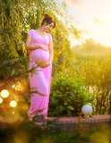 Pregnant happy woman caressing her belly in summer park. Full length pregnant beauty woman outdoor portrait. Healthy pregnancy concept - 217418260