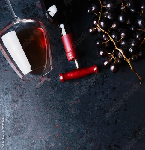 Foto Murales Red wine concept.  Glass with red wine,  bottle and red grape clusters on black rustic background, top view. Place for your design, text, article, advertisement or product.