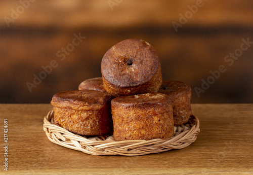 Foto Murales Small cupcakes without cream on a wooden basket. Background is brown. Copy space.