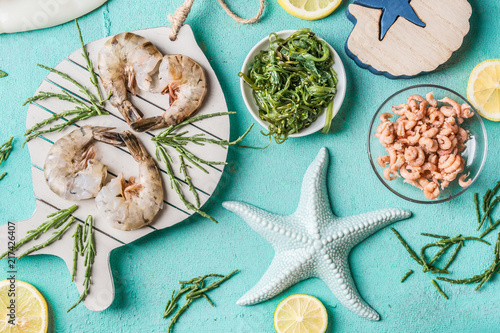 Canvas Tijger Tiger shrimps and North Sea crabs on light blue background with seaweeds in bowls, top view, flat lay. Seafood cooking concept