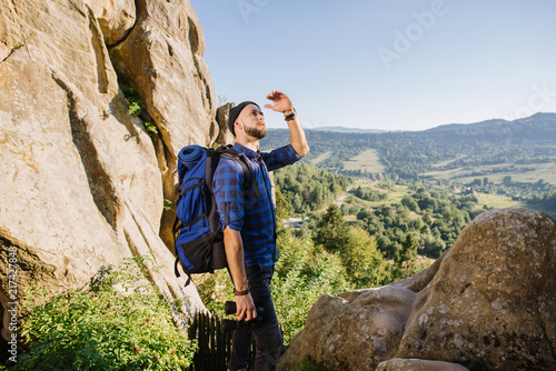 A man traveler with a big backpack looking up on the mountains with beautiful scenic background