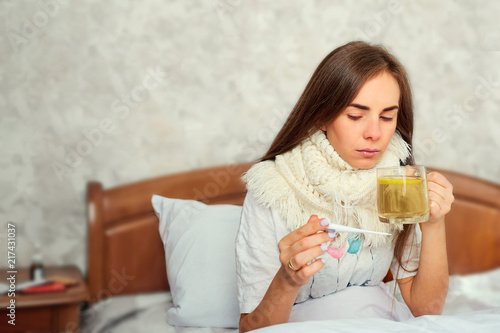 Foto Murales Sick girl with a thermometer on the bed. Virus. Flu.