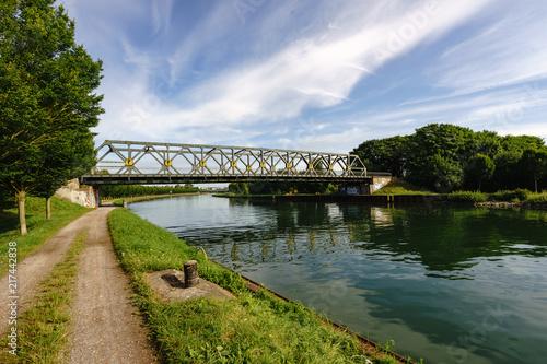 Leinwanddruck Bild Kanal mit Brücke und Wolken