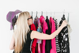 fashion stylist looking for the best outfit for her client. colorful and bright assortment of trendy clothing hanging on the rack.