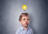 Adorable little kid mull over in front of a grey wall with idea symbol above his head - 217468678