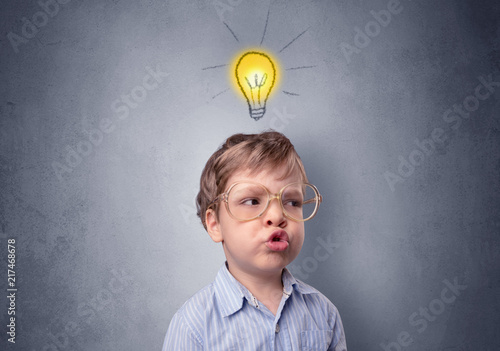 Zobacz obraz Adorable little kid mull over in front of a grey wall with idea symbol above his head