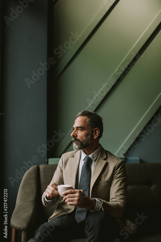 Wall mural Handsome senior businessman drinking coffee in lobby