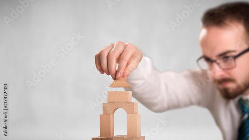 Foto Murales Young handsome businessman using wooden building blocks