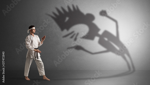 Young karate man fighting with a big black scary shadow