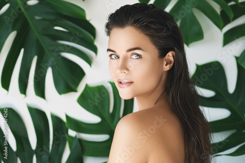 canvas print picture Portrait of young and beautiful woman with perfect smooth skin in tropical leaves