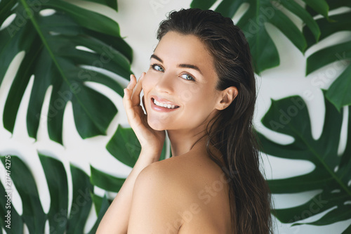 Portrait of young and beautiful woman with perfect smooth skin in tropical leaves - 217474275