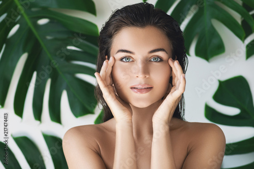 Leinwandbild Motiv Portrait of young and beautiful woman with perfect smooth skin in tropical leaves
