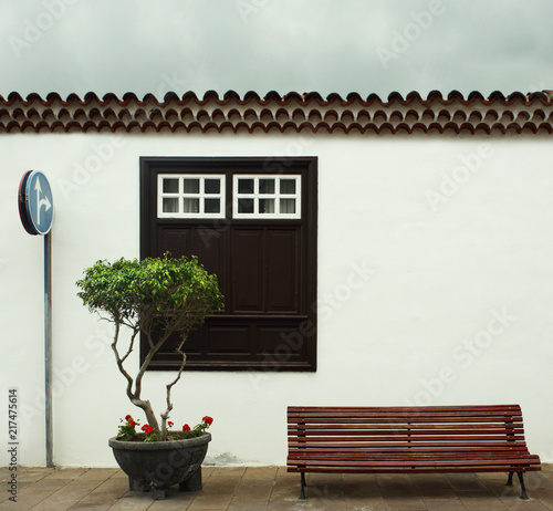 Fotobehang Canarische Eilanden Beautiful detail of a typical facade of a small house with a big window a plant with flowers, tiles roof, a bench and a road sign in Garachico, Tenerife, Canary Island