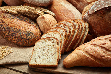 heap of whole and sliced bread on wooden background