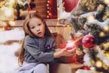 child decorates christmas tree - 217490851