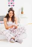 Young woman in pajamas sitting on bed listening to music on headphones using smartphone. Natural and studio lighting.