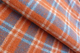 woolen fabric in a cage close-up gray orange stripes squares drape nap vintage coat plaid background for decor rolls cloth folds on fabric natural material