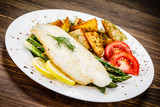 Fish dish - fried fish fillet with fried potatoes and vegetables - 217518036