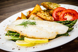 Fish dish - fried fish fillet with fried potatoes and vegetables - 217518092