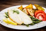 Fish dish - fried fish fillet with fried potatoes and vegetables - 217518245