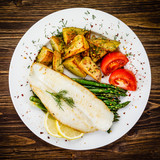 Fish dish - fried fish fillet with fried potatoes and vegetables - 217518275
