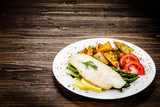Fish dish - fried fish fillet with fried potatoes and vegetables - 217518419